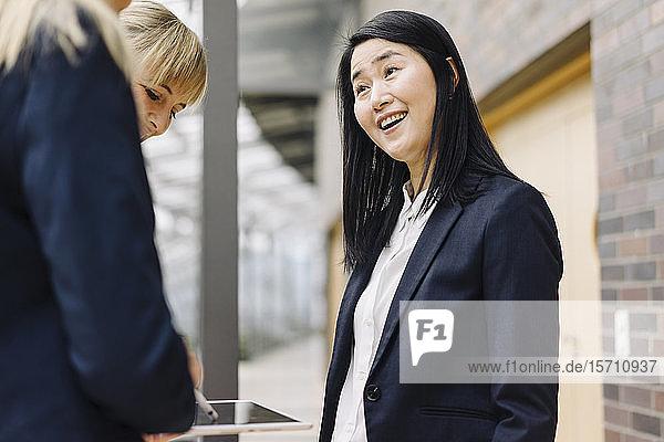 Porträt einer glücklichen Geschäftsfrau mit Kollegen in einem modernen Bürogebäude
