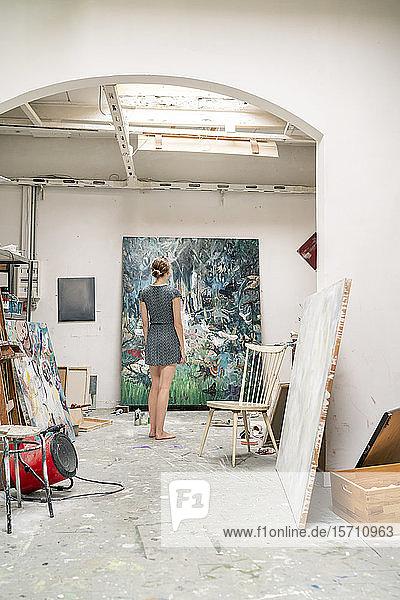 Junge Künstlerin in ihrem Atelier stehend  Malerei betrachtend  Rückansicht