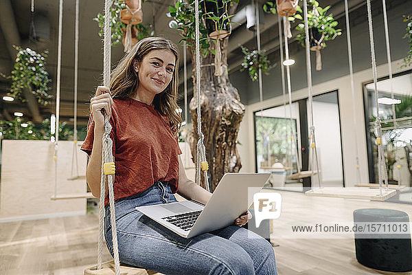 Junge Frau benutzt Laptop und sitzt auf einer Schaukel in einem Büro