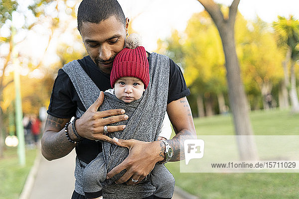 Young father carrying baby son in a baby sling