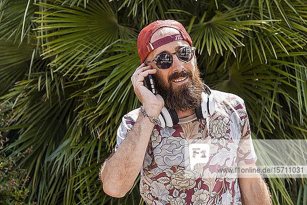 Reifer Mann mit roter Basecap  Sonnenbrille und weißen Kopfhörern mit Smartphone