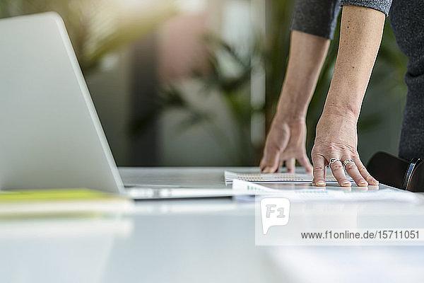 Nahaufnahme einer Geschäftsfrau mit Laptop  die sich im Büro auf den Schreibtisch lehnt