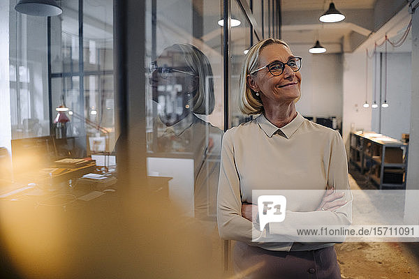 Portrait of smiling mature businesswoman leaning against glass pane in office