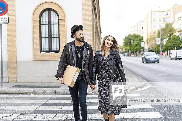 Porträt eines glücklichen jungen Paares beim Überqueren der Straße