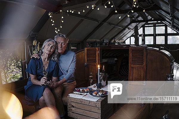 Älteres Ehepaar bei einem Candlelight-Dinner auf einem Boot im Bootshaus