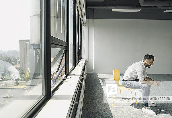 Reifer Geschäftsmann benutzt Mobiltelefon in leerem Büro