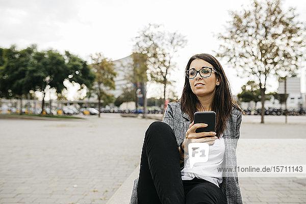 Junge Geschäftsfrau mit Smartphone  die in der Stadt auf einer Bank sitzt