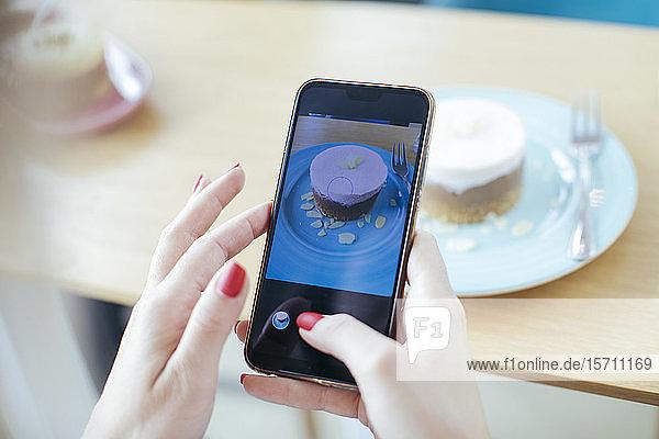 Junge Frau fotografiert ihren Kuchen im Café