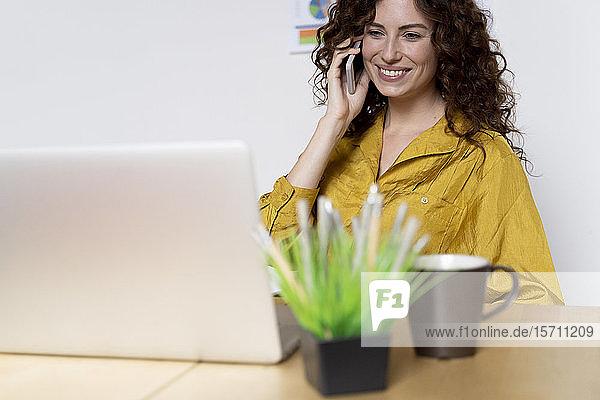Lächelnde Frau mit Laptop und Smartphone am Schreibtisch im Büro