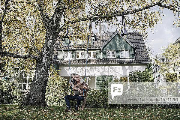 Happy woman embracing senior man on a swing in garden