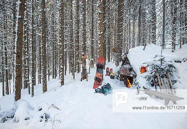 Österreich  Salzburg  Altenmarkt im Pongau  Wintersportgeräte vor verschneiter Waldhütte liegend