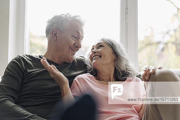 Glückliches älteres Ehepaar entspannt sich zu Hause auf der Couch