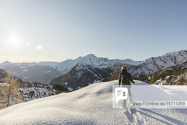 Woman walking with snowshoes in fresh snow in the mountains  Valmalenco  Italy