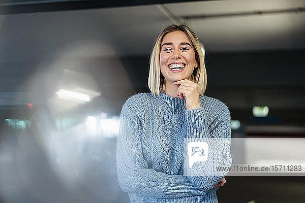 Porträt einer lachenden jungen Frau in einem Parkhaus