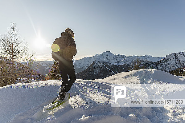 Woman walking with snowshoes in fresh snow in the mountains at sunset  Valmalenco  Italy