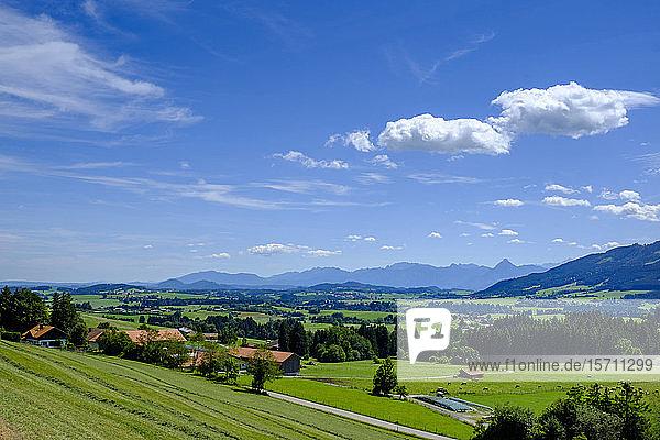 Deutschland  Bayern  Mittelberg  Himmel über ländlichem Dorf mit Bergen im Hintergrund