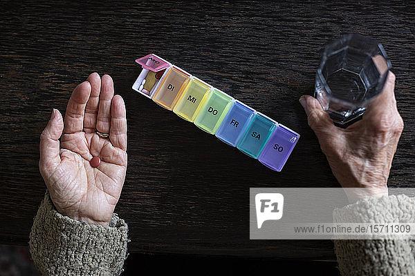 Ältere Frau  die Medikamente einnimmt  Organisatorin von Wasserglas und Pillen