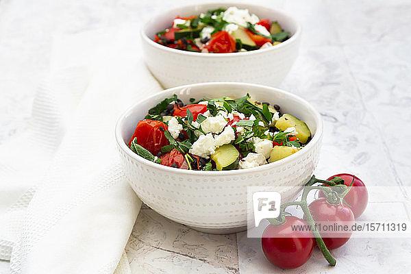 Salatschüsseln mit Beluga-Linsen  Tomaten  Paprika  Zucchini  Schafskäse  Minze und Petersilie