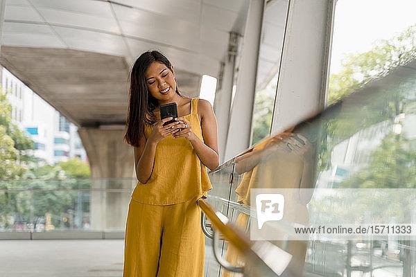 Porträt einer modischen Frau auf einer Terrasse mit Blick auf ihr Handy