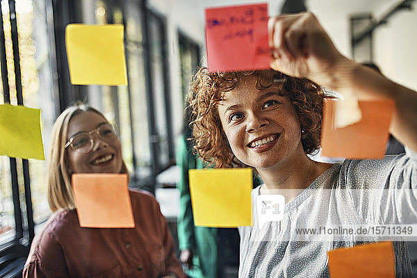 Happy colleagues with sticky notes at glass pane in office