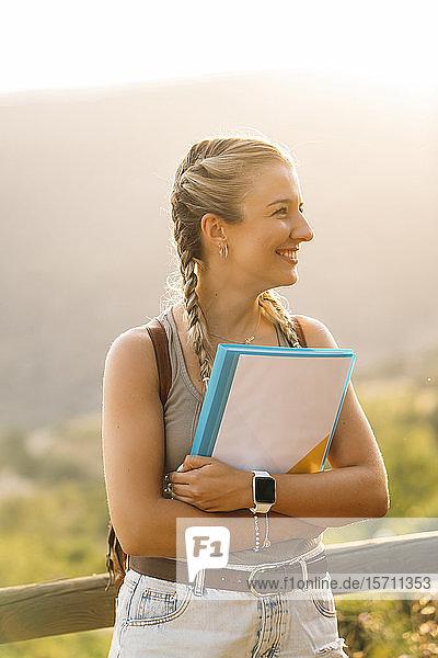 Lächelnde Frau mit Mappe in ländlicher Landschaft