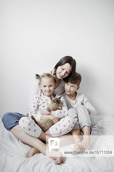 Mutter mit zwei Kindern und einer auf dem Bett sitzenden Katze