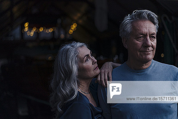Woman looking at senior husband outdoors at night