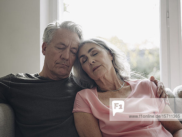 Senior couple napping on couch at home