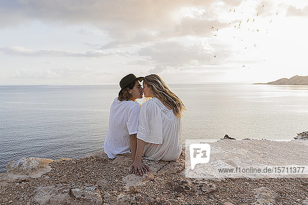 Back view of young couple in love sitting on rock in front of the sea  Ibiza  Balearic Islands  Spain