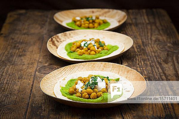 Fladenbrote mit Avocadocreme  Kurkuma  Kichererbsen  Joghurt und Petersilie auf Palmblatttellern