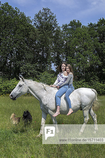 Portrait of two best friends riding together on a horse