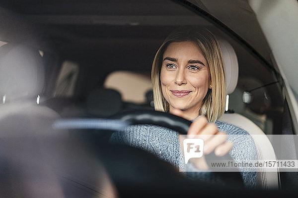 Porträt einer lächelnden jungen Frau am Steuer eines Autos