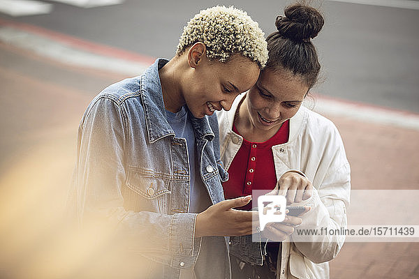 Two young women checking smartphone in the city