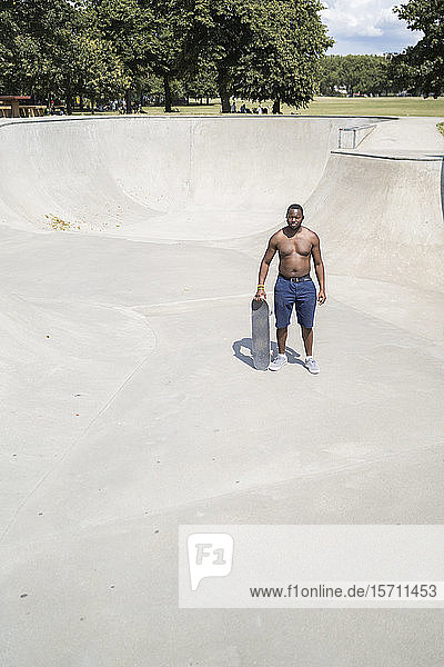 Mann mit Skateboard im Skatepark