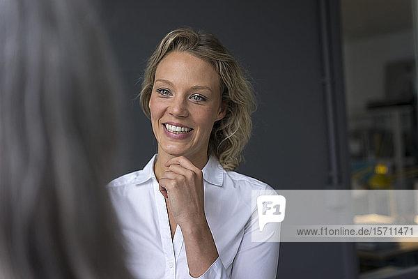 Lächelnde junge Geschäftsfrau schaut Kollegin an