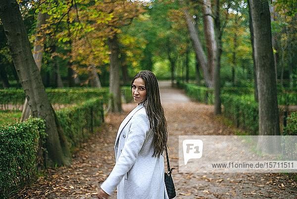 Porträt einer Frau  die in einem Park spazieren geht