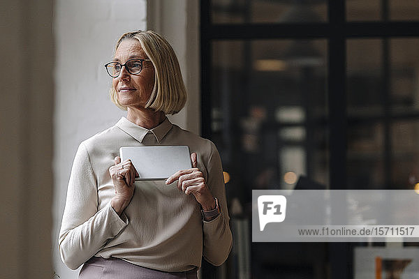 Mature businesswoman holding tablet at the window in office