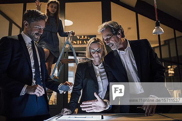 Geschäftsleute diskutieren an glänzender Tafel im Büro mit daneben stehendem Mädchen auf Leiter