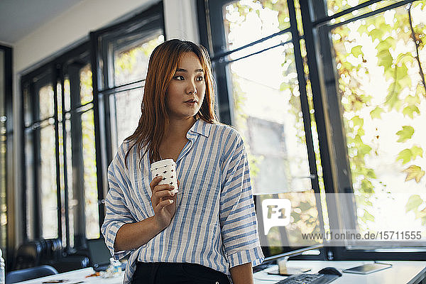 Geschäftsfrau mit Kaffeepause im Büro