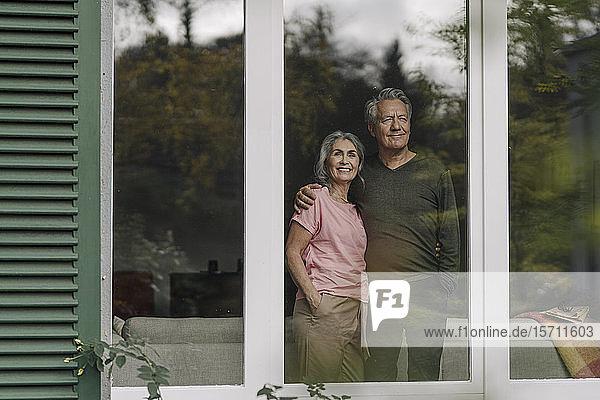 Älteres Ehepaar hinter der Fensterscheibe seines Hauses mit Blick nach draußen