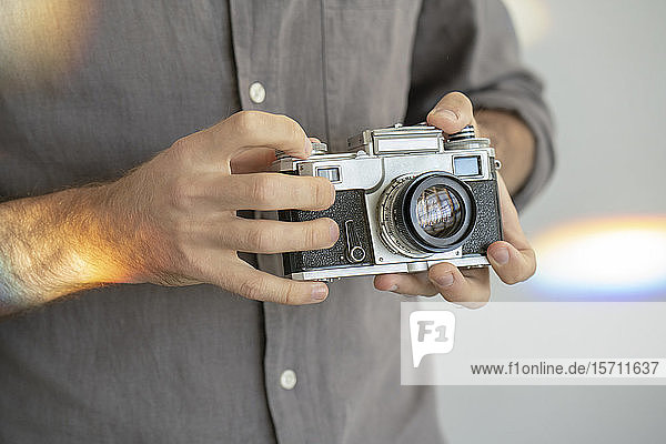 Close-up of man holding old-fashioned camera
