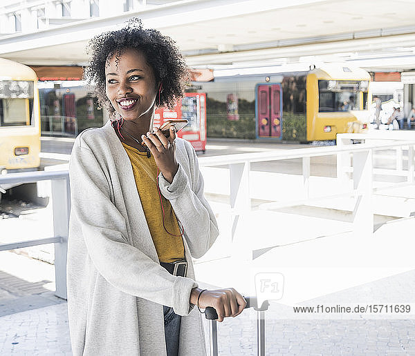 Happy young woman with earphones using smartphone at station platform