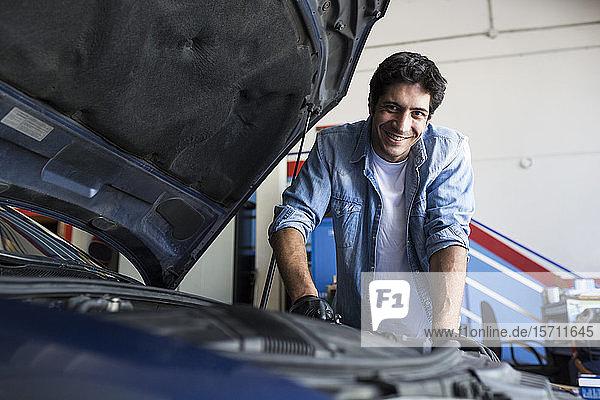 Fröhlicher Mann arbeitet in Autowerkstatt und repariert Automotor mit Werkzeug und lächelt in die Kamera