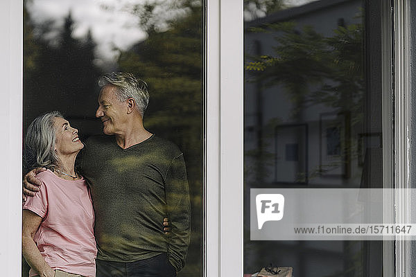 Happy senior couple behind windowpane of their home