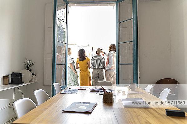Rückansicht von vier Frauen  die auf dem Balkon vor dem Konferenzraum stehen