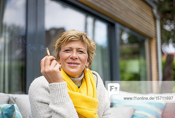Portrait of woman smoking a cigarette on terrace at home