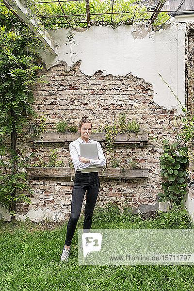 Junge Frau steht im Hinterhof und hält ein digitales Tablet