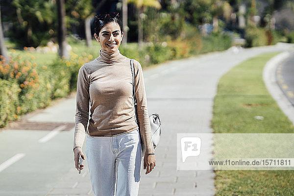 Lächelnde junge Frau geht auf einem Weg