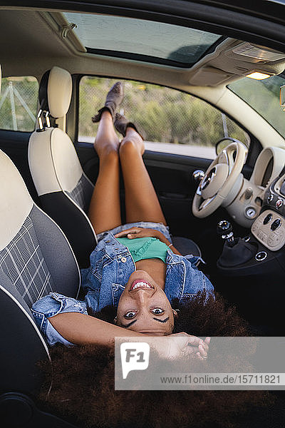 Junge Frau während einer Autofahrt  im Auto liegend