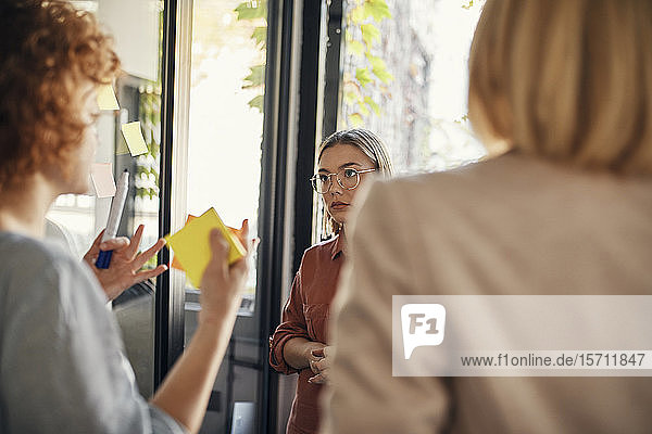 Colleagues with sticky notes discussing in office